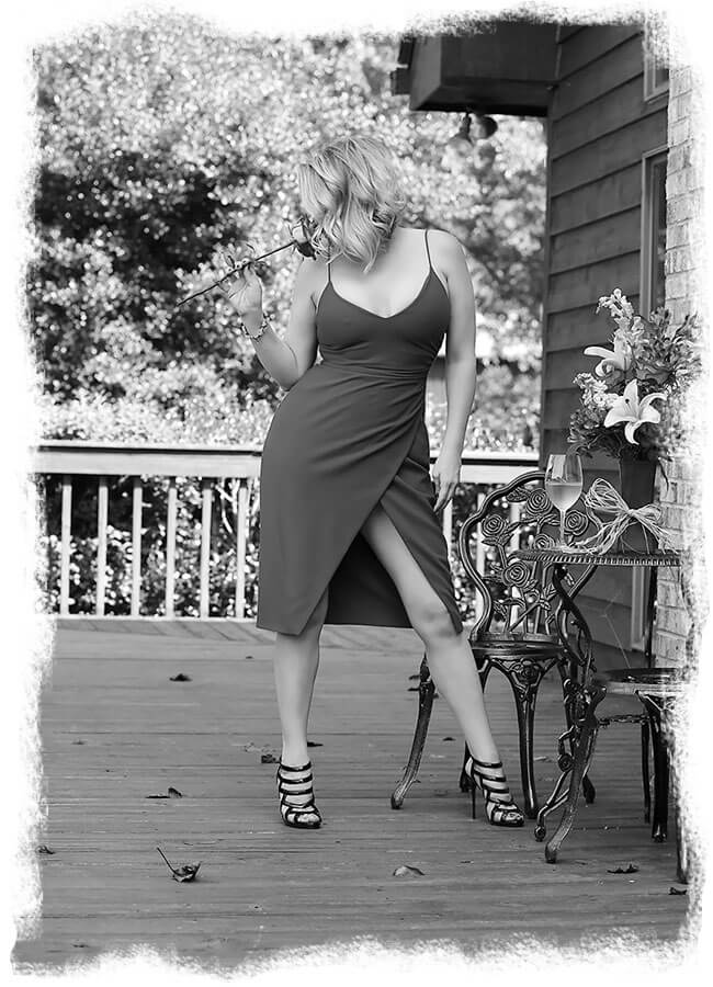 Megan Love, Nashville escort and female companion smelling a rose and wearing a sexy dress on a wooden deck - black & white photo
